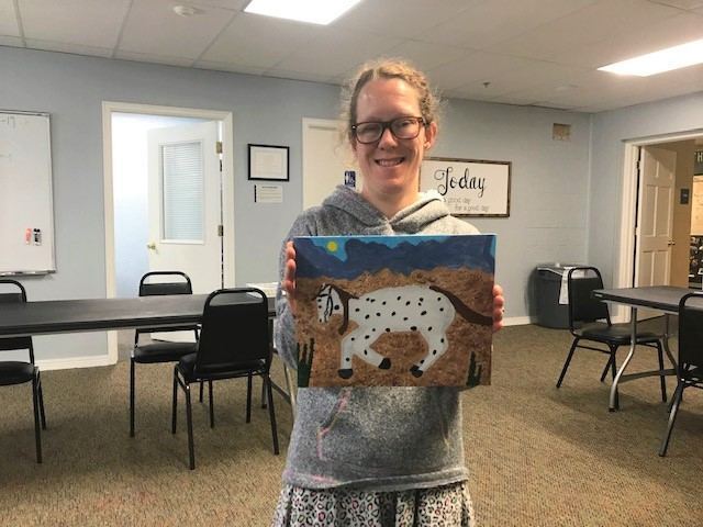 Student goal: Patricia holding her painting of a horse.